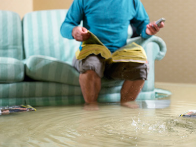 Man Ankle Deep in Water Calling for Emergency Plumbing Service